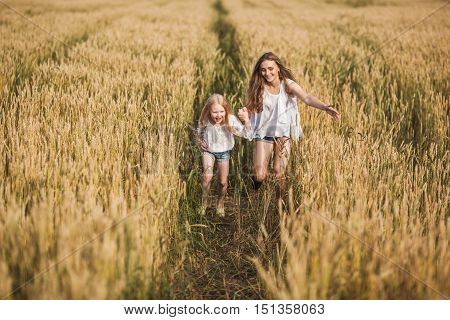 two happy sisters running on wheat filed run on wheat field