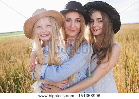 beautiful young mother and her daughters at the wheat field on a sunny day