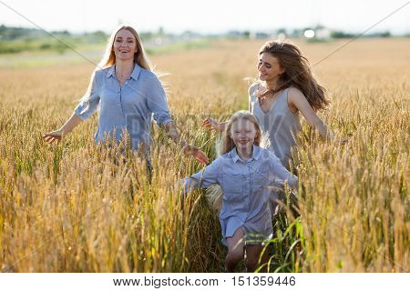 beautiful young mother and her daughters running at the wheat field on a sunny day