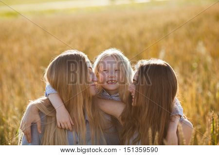 beautiful young mother and her daughters hugging at the wheat field on a sunny day, little girl in center