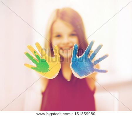 education, art, people, childhood and drawing concept - little happy student girl showing painted hands