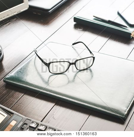 Desktop with leather folder glasses calculator and notepad with pen close up