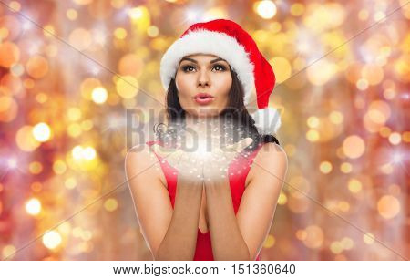 people, holidays, christmas and celebration concept - beautiful sexy woman in santa hat and red dress blowing fairy dust or snowflakes off her palms over lights background