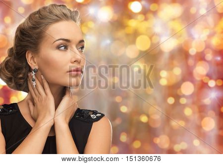 beauty, luxury, people, holidays and jewelry concept - beautiful woman with gem stone earrings over lights background