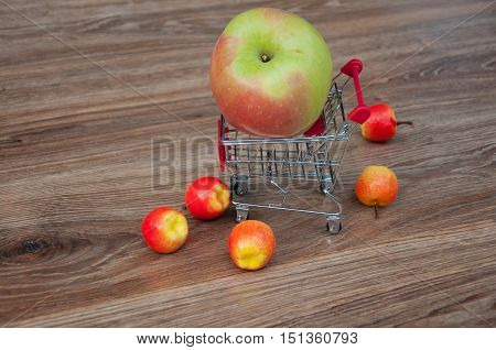 Big apple in shopping cart and small apples around it on wooden background