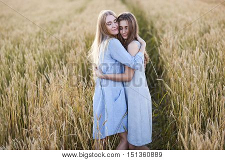 beautiful young mother and her teen daughter at the wheat field on sunset