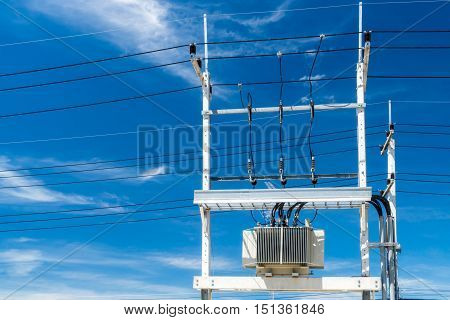 High voltage electrical transformers on utility poles.
