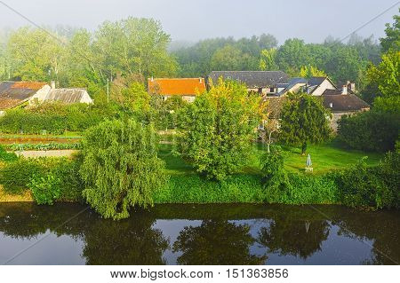 Small French Village on the River Bank in the Morning Mist