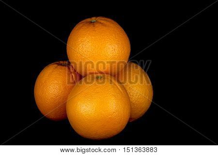 Organic oranges isolated against a black background