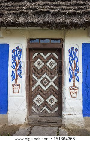 Decorated door of the old traditional Ukrainian house built in wattle and daub technique with thatched roof.