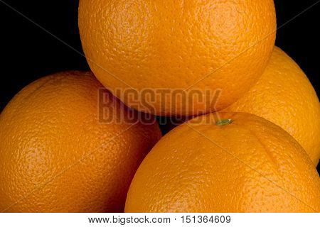 Stack of fresh oranges isolated against a black background
