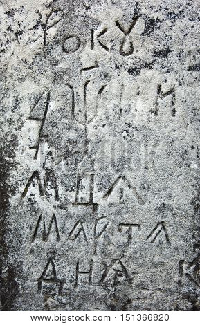 The surface of the old cross gravestone with engraved Old Church Slavonic inscriptions. Kyiv Ukraine. Close up. poster