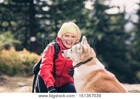 Woman hiking with akita inu dog on forest trail. Friendship recreation and healthy lifestyle outdoors autumn woods in mountains inspirational nature. Fitness and trekking and activity concept.