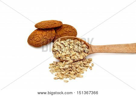 wooden spoon with oatmeal and oatmeal cookies on a white background