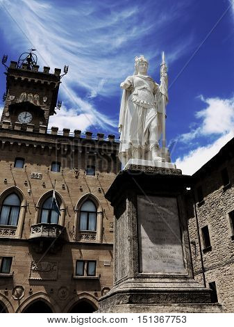 Statue  in San Marino Country and the ancient palace called Palazzo Pubblico seat of Government in Central Italy