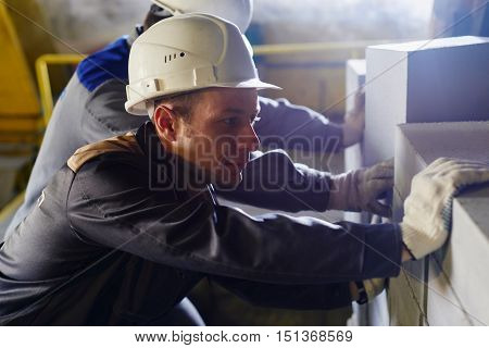 Portrait of worker in hard hat and overalls pushing a cart with bricks closeup