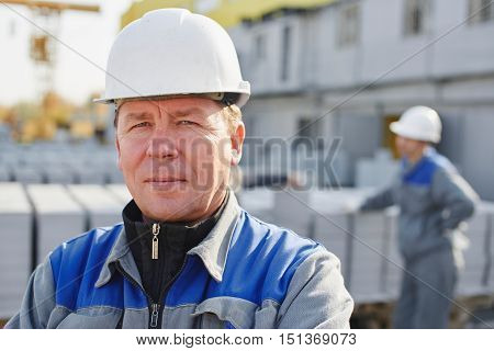 Portrait of a Builder in overalls and helmet on the background of a group of people around a cart with a brick