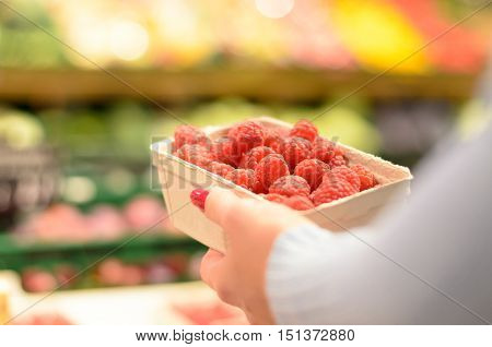 Person Selecting A Punnet Of Fresh Raspberries