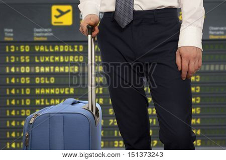 Business trip.  Businessman with travel bag over airport background
