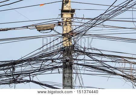 Messy electrical cables and wires on electric pole.