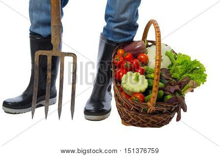 boots stand with fork next to a basket of vegetables