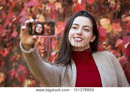 Beautiful young brunette caucasian woman taking selfie with smartphone outdoors in park in autumn. Selfie autumn. Autumn people technology lifestyle concept. Young woman making selfie. Autumn selfie portrait