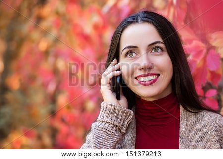Young smiling woman talking on cell phone in the autumn park. Joyful woman is talking on a smart phone outdoors in a bright red leaves in fall. Portrait of girl in autumn park talking on mobile phone. Copy space
