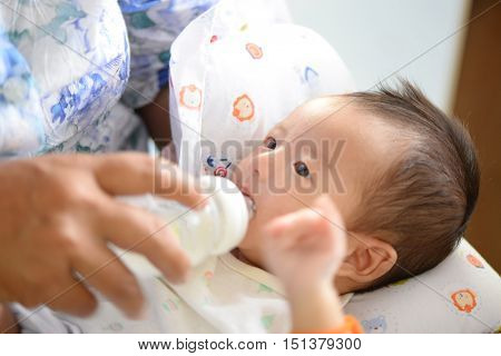 Mother Feeding Her Baby Infant From Bottle, Baby Drinking Milk From Bottle, Warm Tone