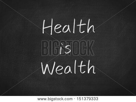 health is wealth text on blackboard background