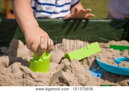 Toddler's hands playing with kinetic sand outdoors. Child making shapes. Lifestyle and summer concept.