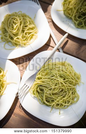 Delicious Italian pasta with green pesto. Spaghetti with homemade basil pesto sauce. Healthy dinner or lunch. Homemade food on wooden table background
