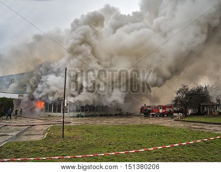 Fire and strong smoke covered building. Dangerous situation