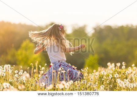 Girl running on the field of dandelions on summer sunset. Beautiful little kid girl dancing on dandelion meadow with summer sunset. Summer fun outdoors.