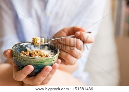 Young woman with muesli bowl. Girl eating breakfast cereals with nuts pumpkin seeds oats and yogurt in bowl. Girl holding homemade granola. Healthy snack or breakfst in the morning..
