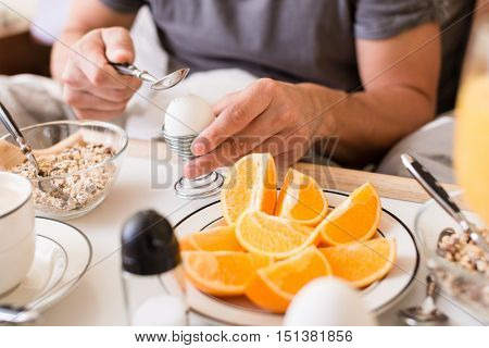 Man cracking open a boiled egg for breakfast using a spoon with cereal and fresh oranges on the table in a healthy diet and lifestyle concept