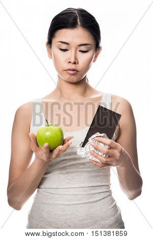 Pretty Asian woman debating an apple or chocolate as she stands with a fresh green apple in one hand and unwrapped bar of candy in the other in a healthy diet concept