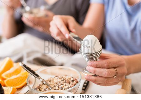 Woman opening a boiled egg in an eggcup for breakfast using a knife with selective focus to her hands