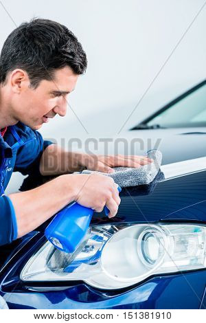 Man cleaning his luxury blue sedan car with a sponge and spray bottle as he works around the front headlamp