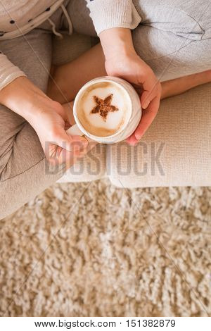 Girl with coffee mug sitting on the sofa indoors. Woman drinking a cup of coffee or tea sitting cozy at home. Relax and rest. Capuccino with cinnamon star. top view