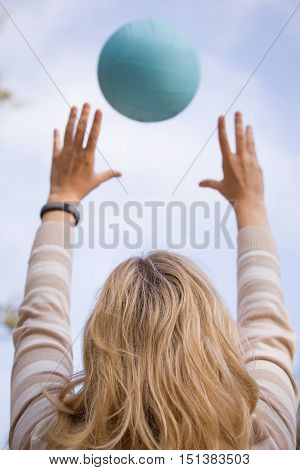 Young blond woman throwing a blue ball into the sky. Close-up of a woman playing volleyball on the sunny simmer day. Outdoors. Hands and ball.