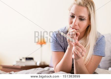 Worried young woman checking her temperature on a handheld thermometer to see if she has a fever in a healthcare and medical concept