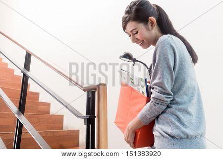 Young Indonesian girl carrying moving boxes up the stairs