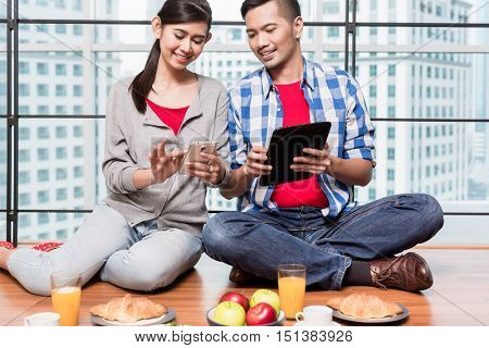 Young indonesian couple, woman and man, having breakfast in their apartment in front of city skyline