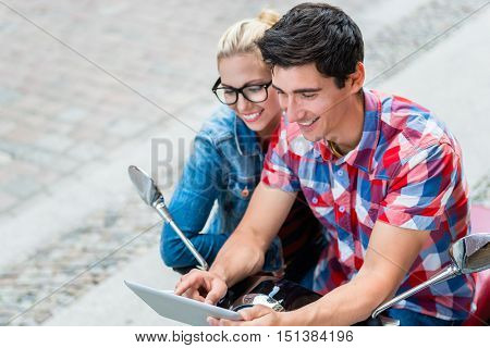 Young Couple, woman and man, on city trip in Berlin planning their Vespa tour using tablet PC