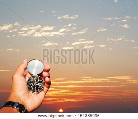 Man hand with a black and silver compass in sunset background.