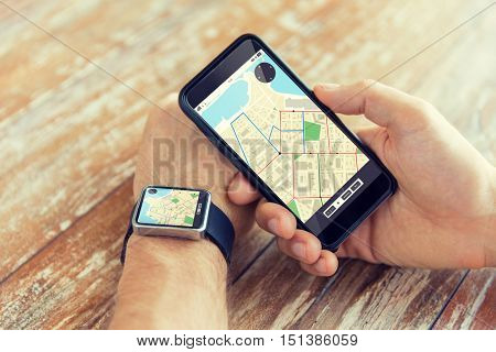 people, modern technology, application and navigation concept - close up of male hand holding smart phone and wearing watch with gps and road map on screen