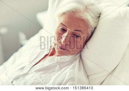 medicine, age, health care and people concept - senior woman patient lying in bed at hospital ward