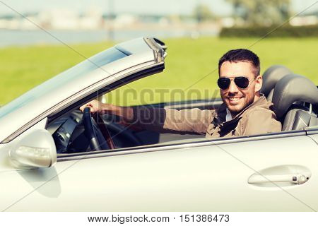 auto business, transport, leisure and people concept - happy man driving cabriolet car outdoors
