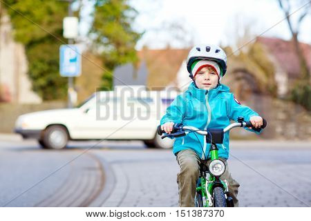 Little preschool kid boy biking with bicycle over the street in the city. Dangerous situation with cars and traffic for children