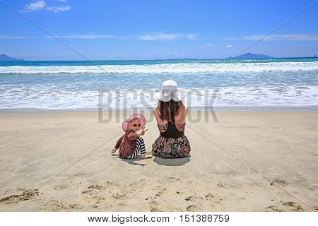 Young Pretty Woman With Little Daughter Sitting On Sandy Beach